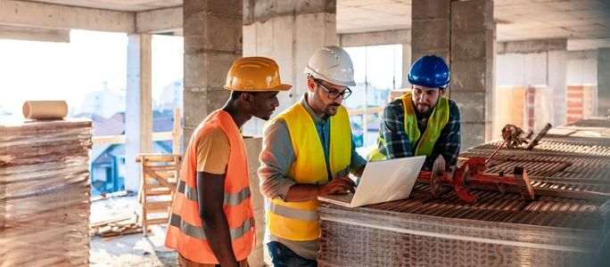 Construction Workers Collaborating on Laptop