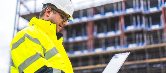 Construction worker viewing a tablet on site